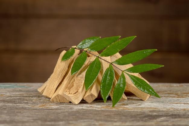Eurycoma longifolia jack, racines séchées et feuilles vertes sur un vieux fond en bois.