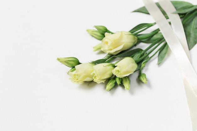 Eustoma fleurs blanches fraîches sur fond blanc avec espace de copie. jeunes boutons floraux tendres.