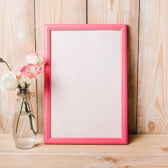 Eustoma fleurs dans un vase près du cadre blanc blanc sur fond en bois