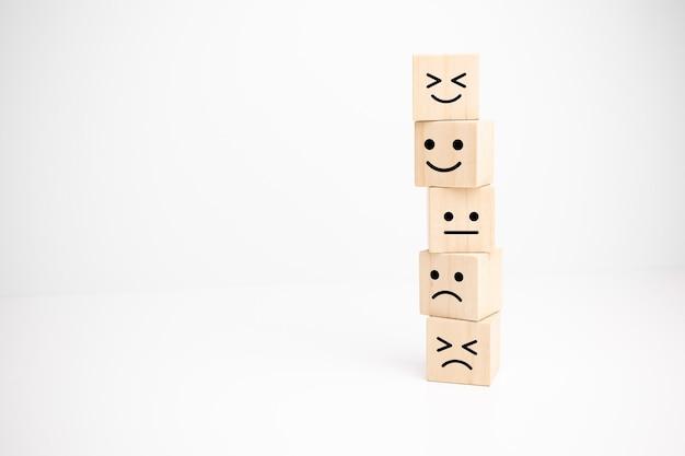 Évaluation du service client et concepts d'enquête de satisfaction. la main du client a choisi le symbole du visage souriant du visage heureux sur un cube en bois, espace de copie