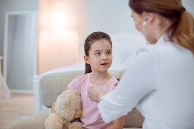 Évaluation de la santé. focused belle fille assise sur fond flou et ouverture de la bouche tandis que femme médecin à l'aide d'un stéthoscope