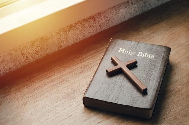 L'évangile avec une croix près du rebord de la fenêtre au coucher du soleil livres dans les enseignements de dieu chrétiens