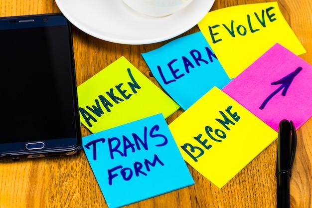 Éveillez-vous, apprenez, évoluez, transformez et devenez - des objectifs ou des résolutions inspirants du nouvel an - des notes autocollantes colorées sur fond de bois.