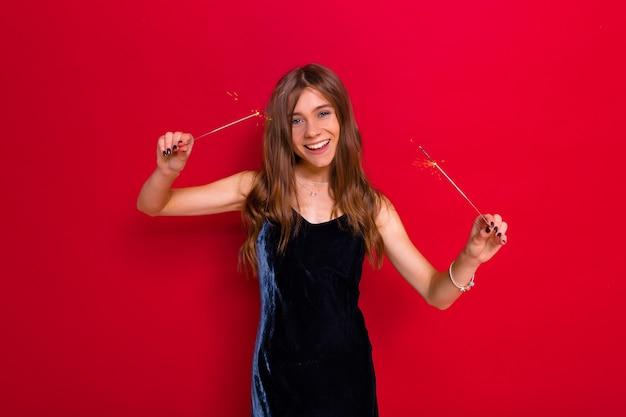 Événement de fête lumineux de joyeuse jeune femme heureuse en élégante robe noire célébrant et s'amusant sur fond rouge isolé avec des cierges magiques.