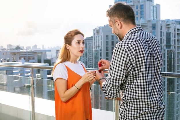 Événement romantique. belle belle femme regardant son petit ami tout en obtenant une proposition de sa part
