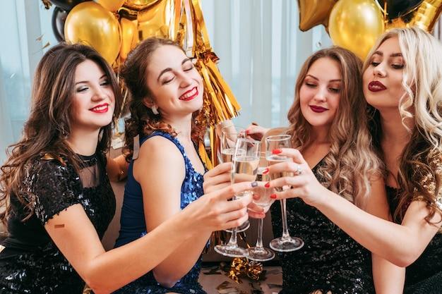 Événement spécial. des dames chics tintant des verres de champagne, buvant des toasts à leur meilleure amie.