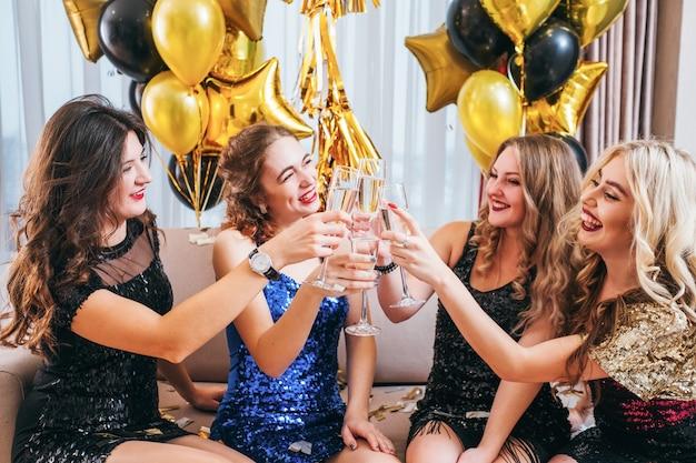 Événement spécial. mesdames traînent, assises dans une chambre décorée de ballons, tintant des verres de champagne.