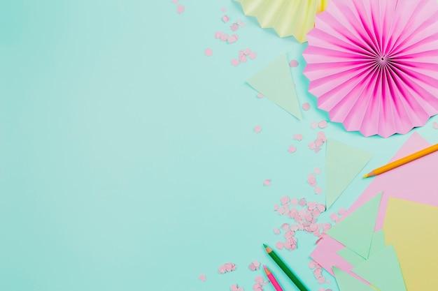 Eventail circulaire en papier rose fait avec du papier sur un fond vert menthe