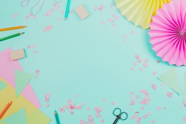 Eventail en papier circulaire avec des confettis et des crayons de couleur sur fond bleu sarcelle