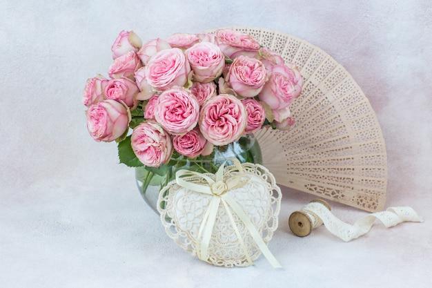 Éventail, ruban de dentelle, coeur et bouquet de roses roses dans un vase rond transparent