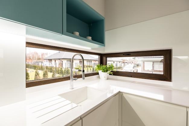 Évier blanc avec robinet et grande fenêtre brune à l'intérieur de la cuisine