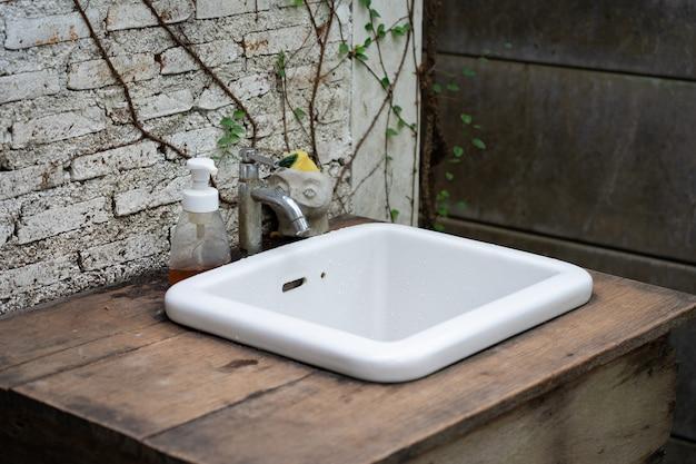 Évier en céramique blanche dans le jardin, jardin vintage