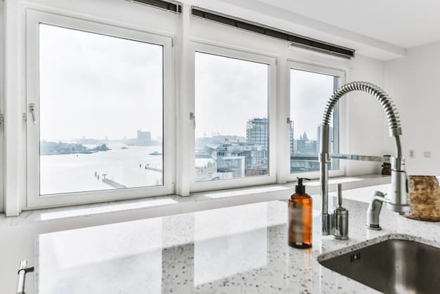 Évier avec robinet brillant installé sous un comptoir moderne près du pot avec des épices et cuisinière à gaz dans la cuisine à la maison
