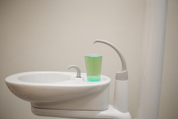 Évier avec un verre d'eau dans le cabinet dentaire
