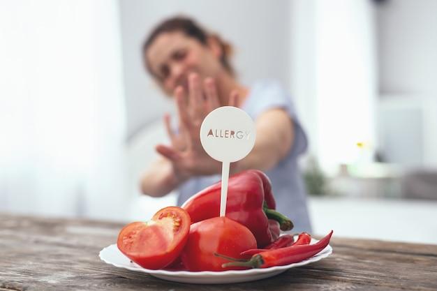 Évitez le rouge. belle jeune femme au foyer à la recherche déterminée à éviter de manger des légumes rouges provoquant sa réaction allergique