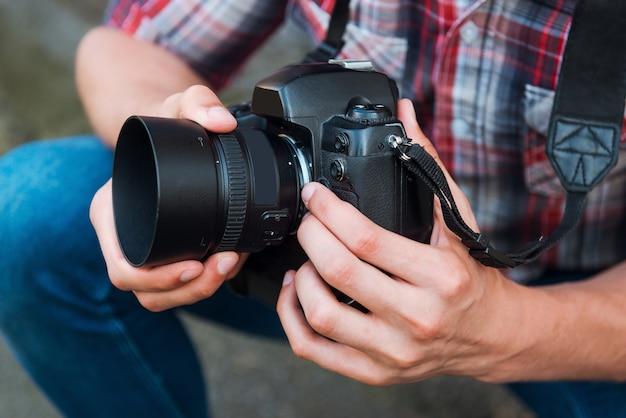Examen de l'appareil photo avant la prise de vue. gros plan d'un homme examinant son appareil photo numérique en se tenant debout à l'extérieur