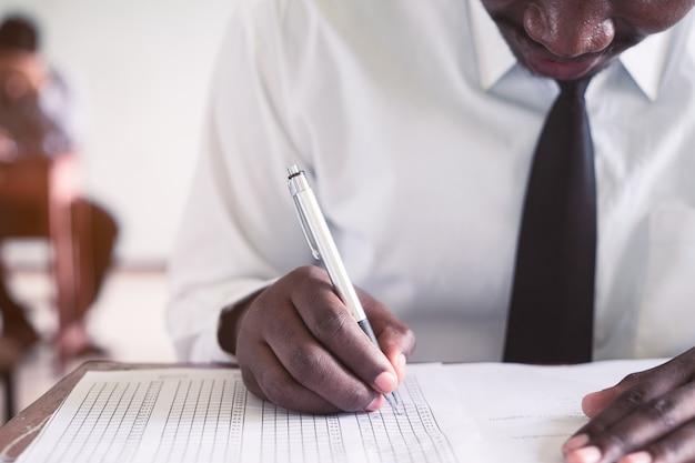 Examen avec homme africain faisant test pédagogique avec le stress en salle de classe.