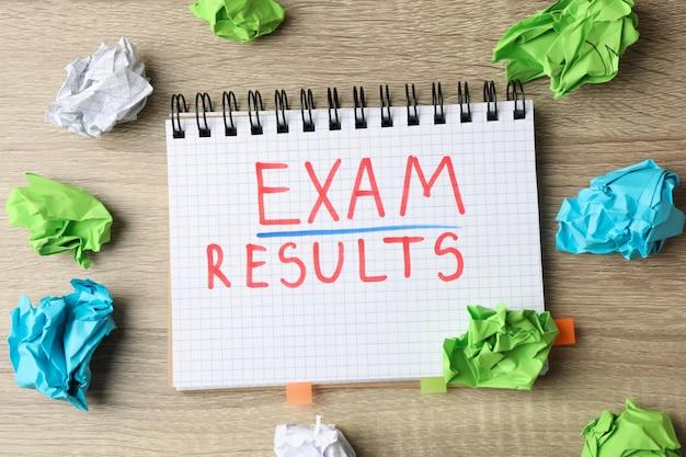 Examen d'inscription, résultats et boules de papier sur bois, vue de dessus