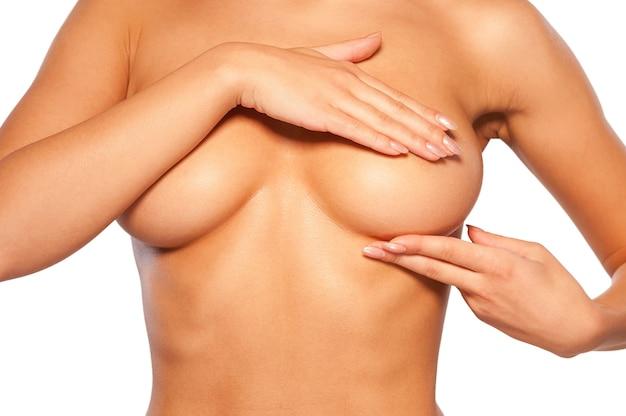 Examen mammaire. image recadrée d'une jeune femme torse nu examinant ses seins en se tenant debout isolé sur blanc