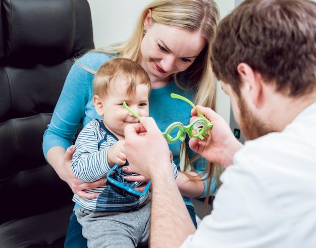 Examen oculaire de base. la mère tient l'enfant pendant l'examen des yeux.