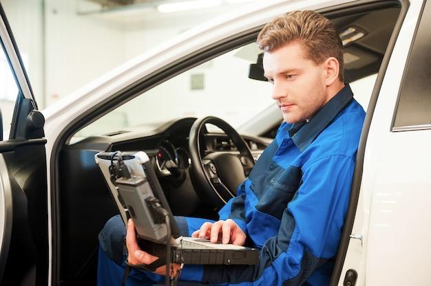 Examen de voiture avec ordinateur spécial. jeune homme confiant travaillant sur un ordinateur portable spécial alors qu'il était assis dans une voiture en atelier