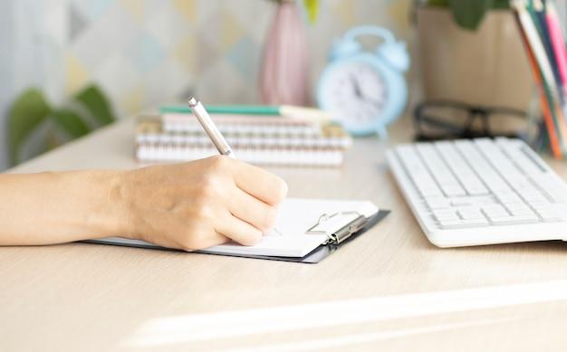 Examens. vue recadrée des élèves qui écrivent un test dans leurs cahiers d'exercices