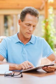 Examiner sa nouvelle tablette. homme mûr confiant travaillant sur une tablette numérique tout en étant assis à la table à l'extérieur avec une maison en arrière-plan