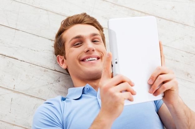 Examiner son nouveau gadget. vue de dessus du jeune homme heureux allongé sur le sol et tenant une tablette numérique