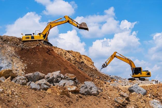 Excavateurs et machine de concassage de pierre de l'exploitation minière sous un ciel bleu avec des nuages