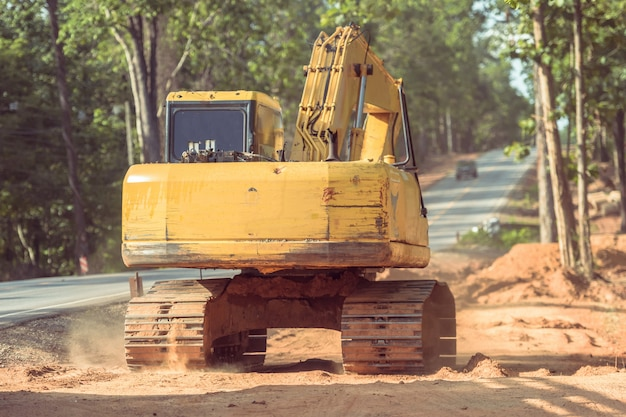 Excavation digger déversant de la terre sur la route.