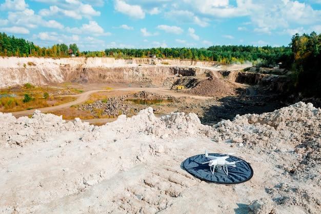 Excavatrice et camions à benne minière lourds dans une carrière de calcaire