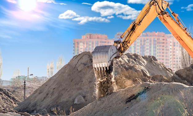 L'excavatrice sur le chantier de construction prend le sable et le gravier de la carrière.