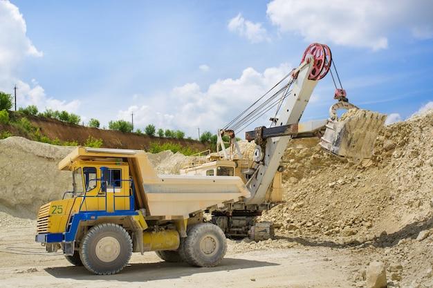 Une excavatrice charge un énorme camion avec de la roche