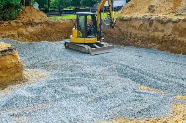 Excavatrice creusant le godet creusant le gravier d'une fondation de bâtiment
