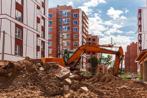 L'excavatrice creuse le sol sur un chantier de construction sur fond d'immeubles de grande hauteur