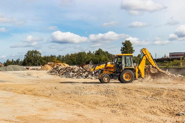 Une excavatrice dans un godet transporte de la terre pour le remblayage sur le chantier de construction. matériel de construction pour les travaux de terrassement.