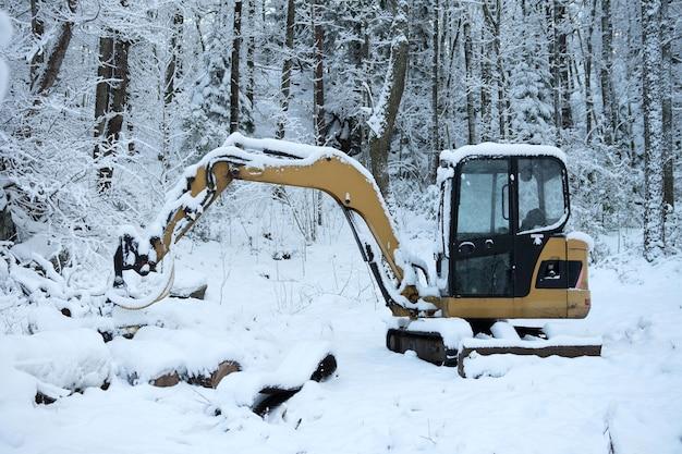 Une excavatrice enlève la neige de la route en hiver