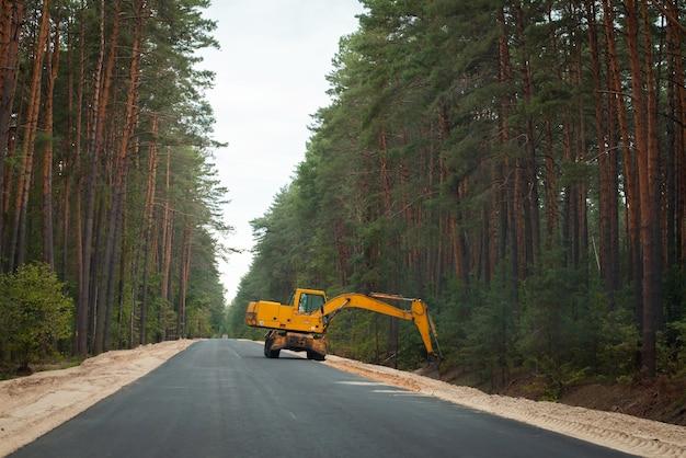 Excavatrice faisant le bord de la route sur la nouvelle route goudronnée