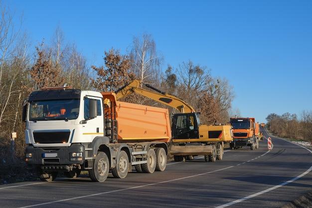 Une excavatrice à godets dégage le bord de la route. travaux routiers. jeter une nouvelle route. chargement d'argile et de pierres d'excavatrice