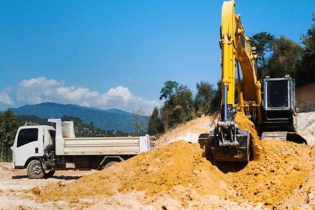 Excavatrice industrielle travaillant sur un chantier de construction pour nettoyer le sol de sable et de terre