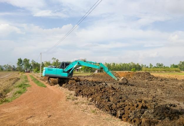 L'excavatrice moderne travaille sur le terrassement pour creuser les étangs près de la rizière