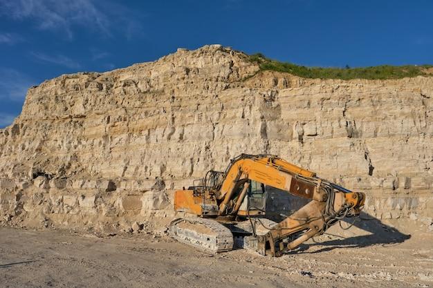 L'excavatrice se dresse sur le fond d'une carrière de pierre.