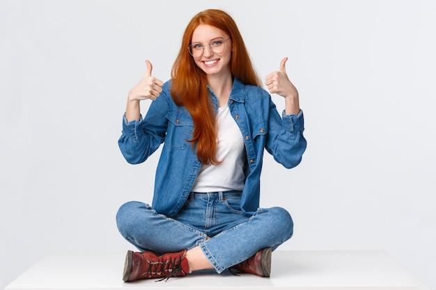 Excellent, concept de satisfaction et de personnes. enchanté petite amie rousse mignonne de soutien assis sur le sol, les jambes croisées dans une pose détendue, approbation souriante, montrant les pouces vers le haut applaudir