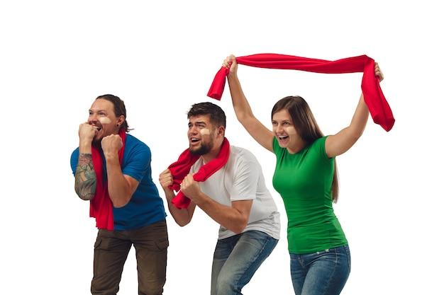 Excellent objectif. trois fans de football femme et hommes acclamant l'équipe de sport préférée avec des émotions vives isolées sur fond de studio blanc