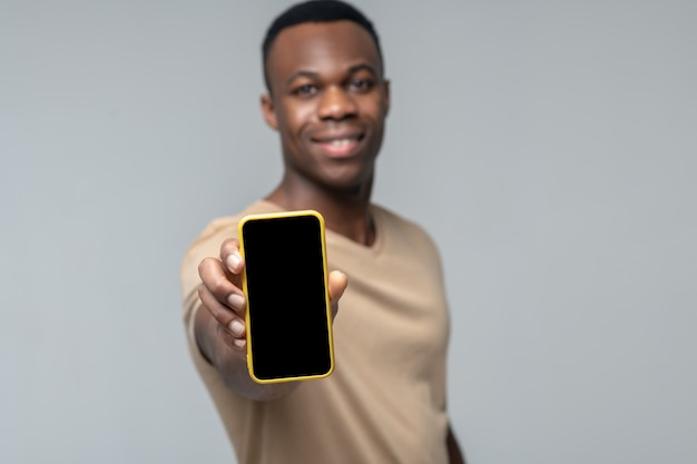 Excellent smartphone. joyeux jeune homme à la peau sombre adulte montrant l'écran du smartphone dans la main tendue sur fond clair