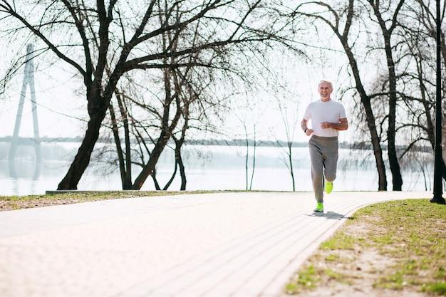 Excellente forme. homme mûr énergique qui court dans le parc en souriant
