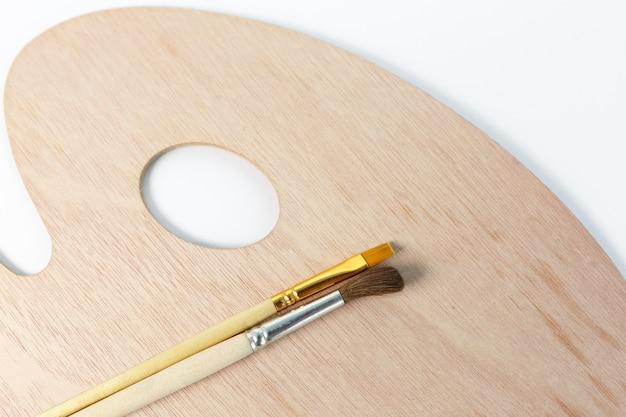 Excellente palette en bois avec des pinceaux sans peinture, sur un blanc