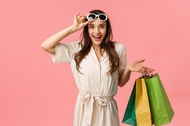 Excellentes réductions, doivent avoir cette saison. séduisante jeune brune en robe, tenant des sacs à provisions, des lunettes de décollage et souriant comme voyant le meilleur prix, mur rose debout