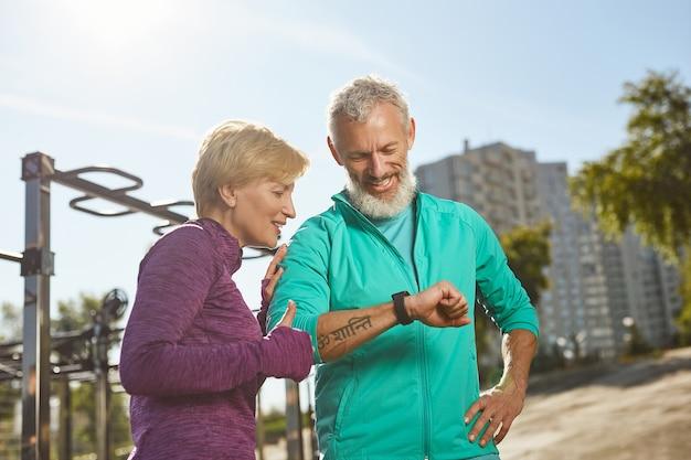 Excellents résultats couple familial d'âge mûr heureux en vêtements de sport regardant smartwatch et vérifiant la formation