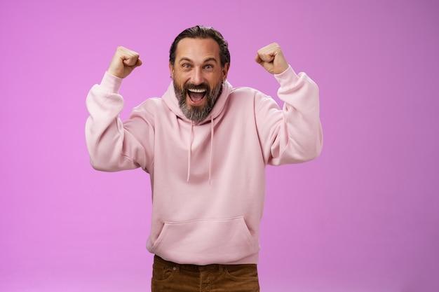 Excité acclamations dévouées mâles cheveux gris barbus hurlant des mots de soutien gagner la place de loterie bon pari chanceux debout heureux triomphant dire oui levant les poings victoire geste de succès, mur violet.